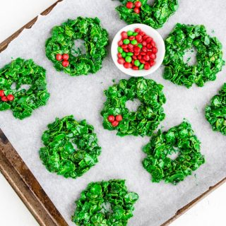 Green Christmas Wreath cookies on a baking sheet with a bowl of red M&M's