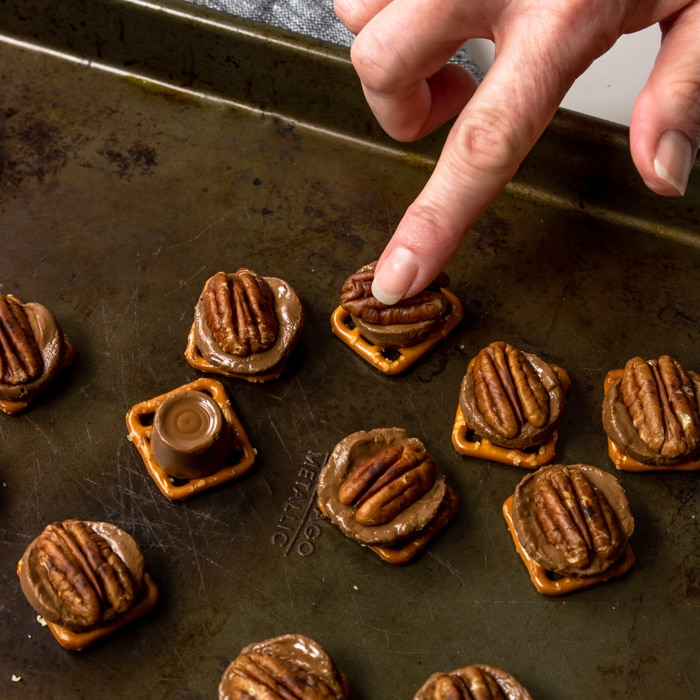 Pressing a toasted pecan into the middle of the soft Rolo on top of a preztel