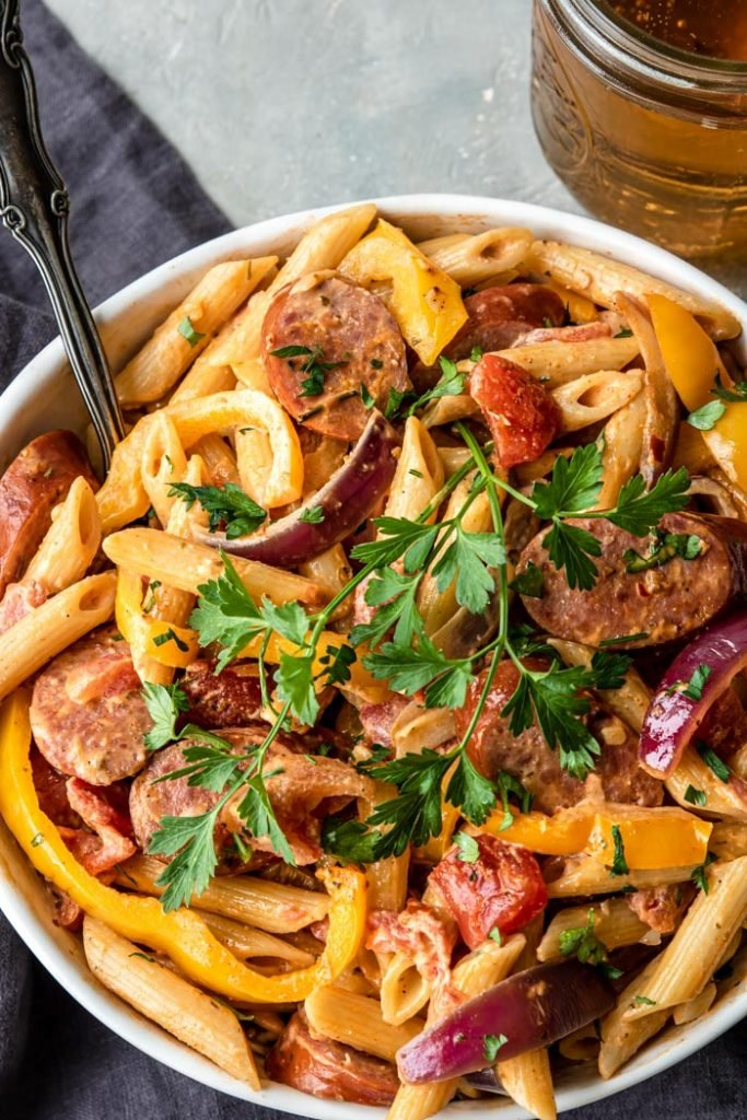 penne pasta, smoked sausage, onions and peppers in a cajun cream sauce in a large white bowl garnished with parsley