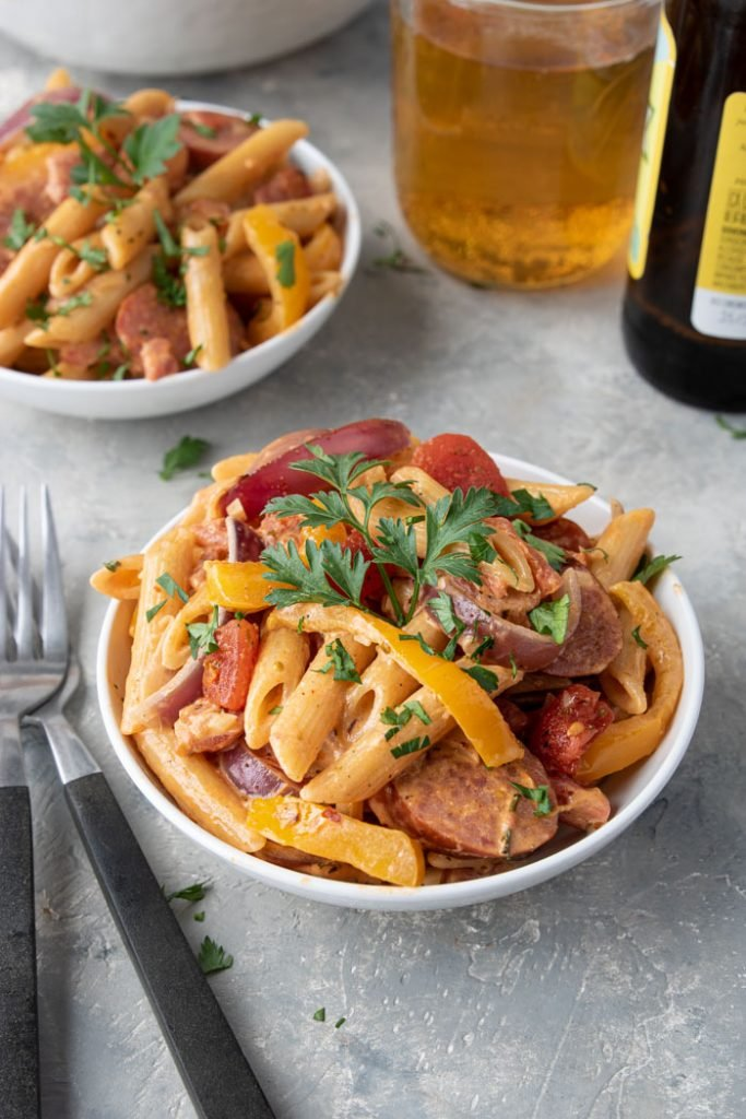 two bowls of creamy cajun pasta with peppers and sausage