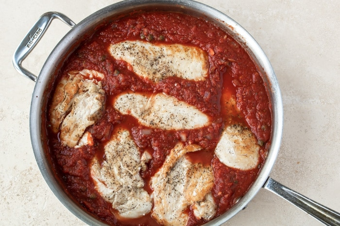 Browned Chicken breasts nestled down in a red wine tomato sauce