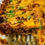 beef enchilada Casserole with a slice cut out so you can see the layers of corn tortillas, beef, cheese and sauce