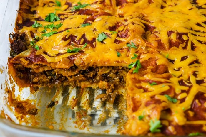 beef enchilada casserole with a piece taken out so you can see the layers of tortillas, beef, cheese, and sauce