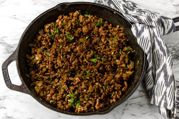 ground beef in a skillet with onions, garlic and cilantro