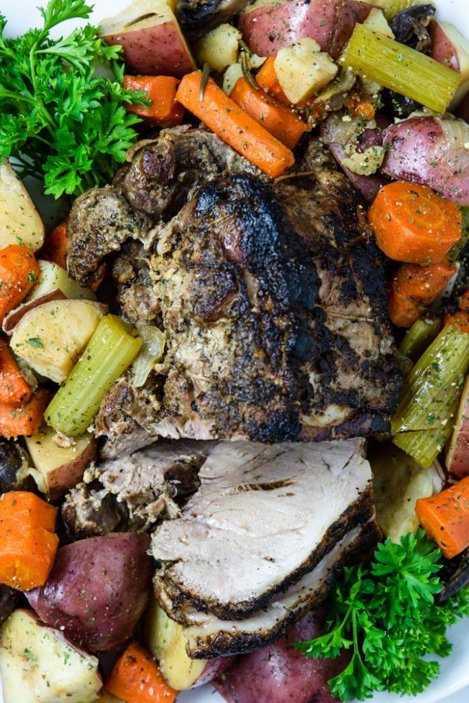 sliced pork roast surrounded by vegetables