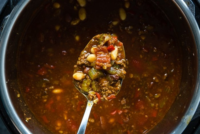 A spoonful of chili over a pot