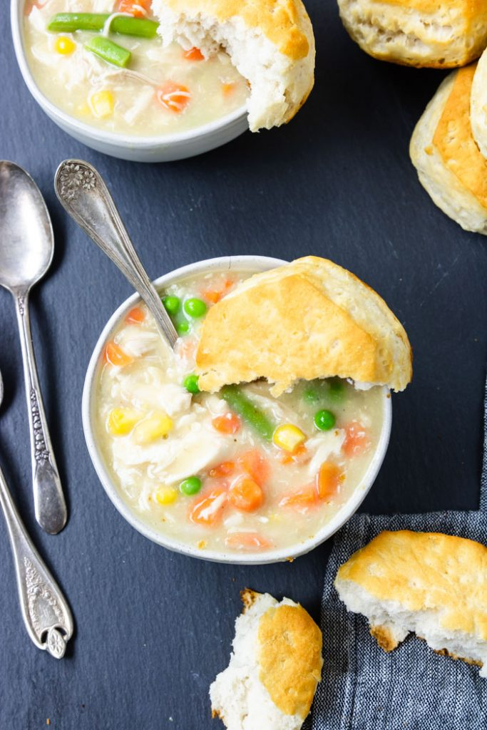 easy chicken and biscuits in a white bowl with half a biscuit on top and a spoon