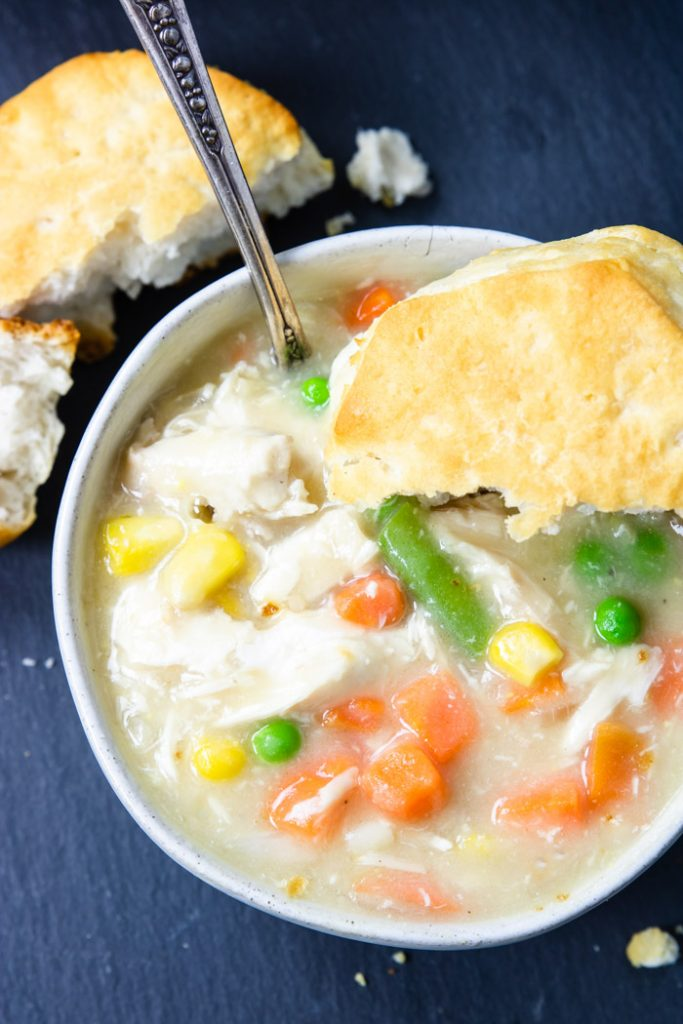 up close picture of chicken stew with a biscuit on top