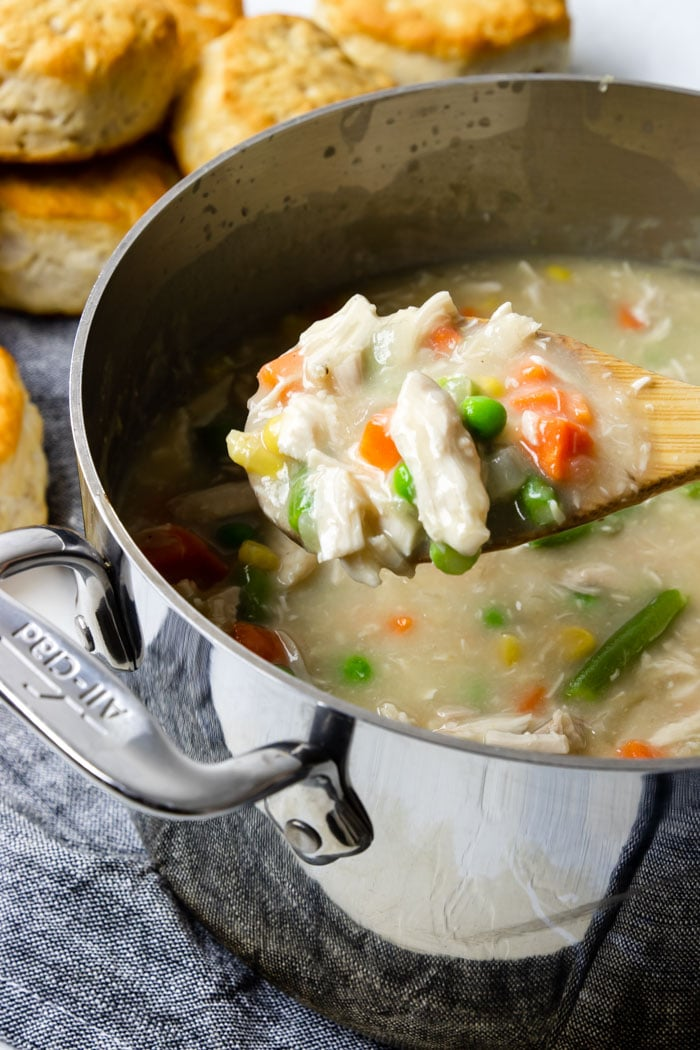 A spoon full of chicken and veggie stew with biscuits in the background