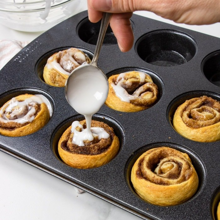 cinnamon rolls in a muffin tin being drizzled with frosting