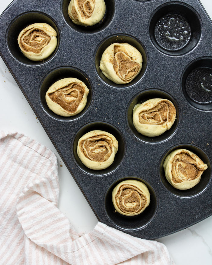 uncooked cinnamon rolls in a muffin tin