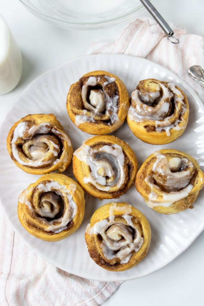 7 crescent cinnamon rolls topped with frosting on a white plate