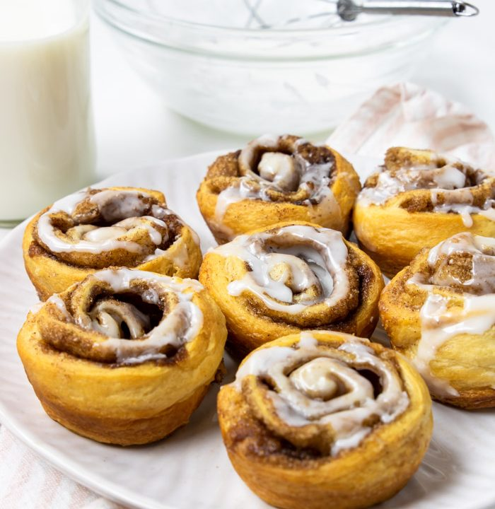 crescent cinnamon rolls on a white plate with frosting in the background