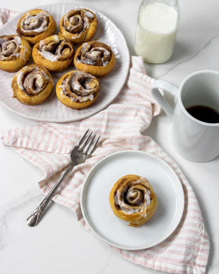 cinnamon roll on a white plate with coffee and a fork