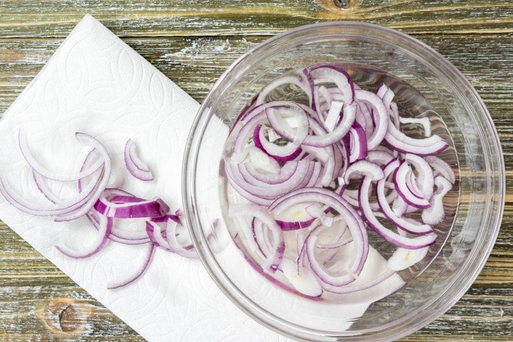raw red onions being rinsed in water