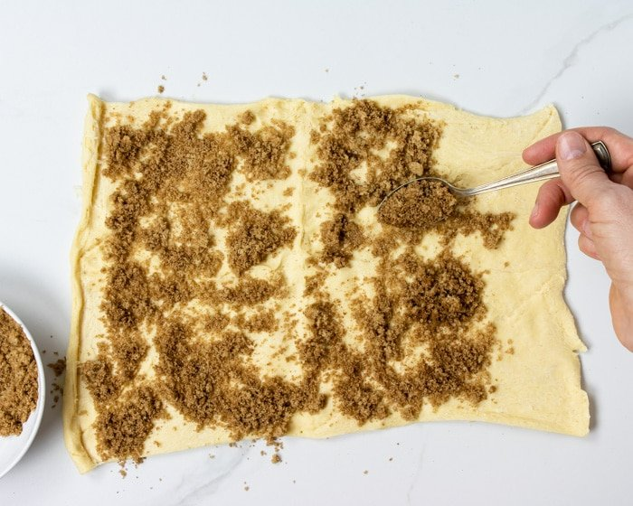 sprinkling cinnamon and brown sugar over the crescent dough