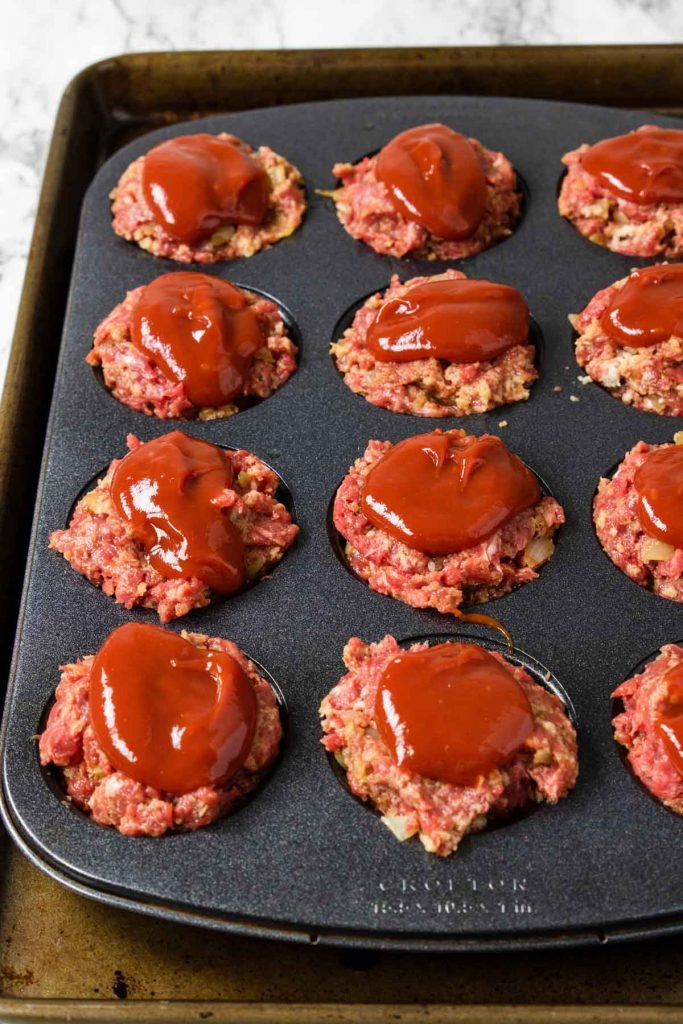 raw meatloaf muffins in a muffin tin topped with ketchup
