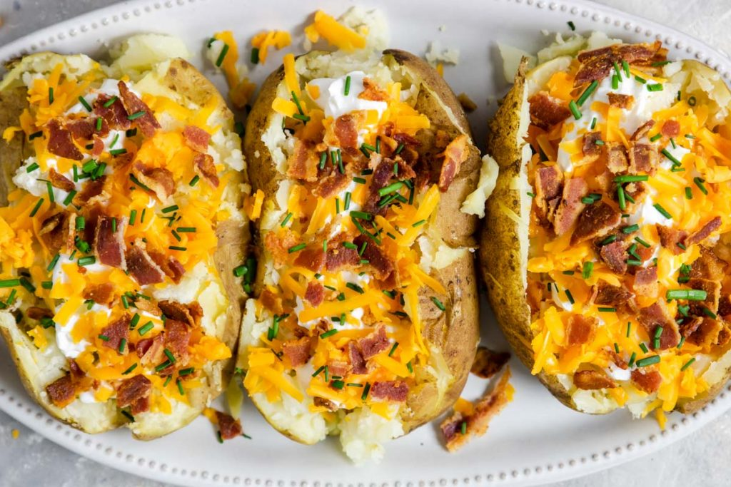 three baked potatoes on a plate stuffed with cheese and bacon