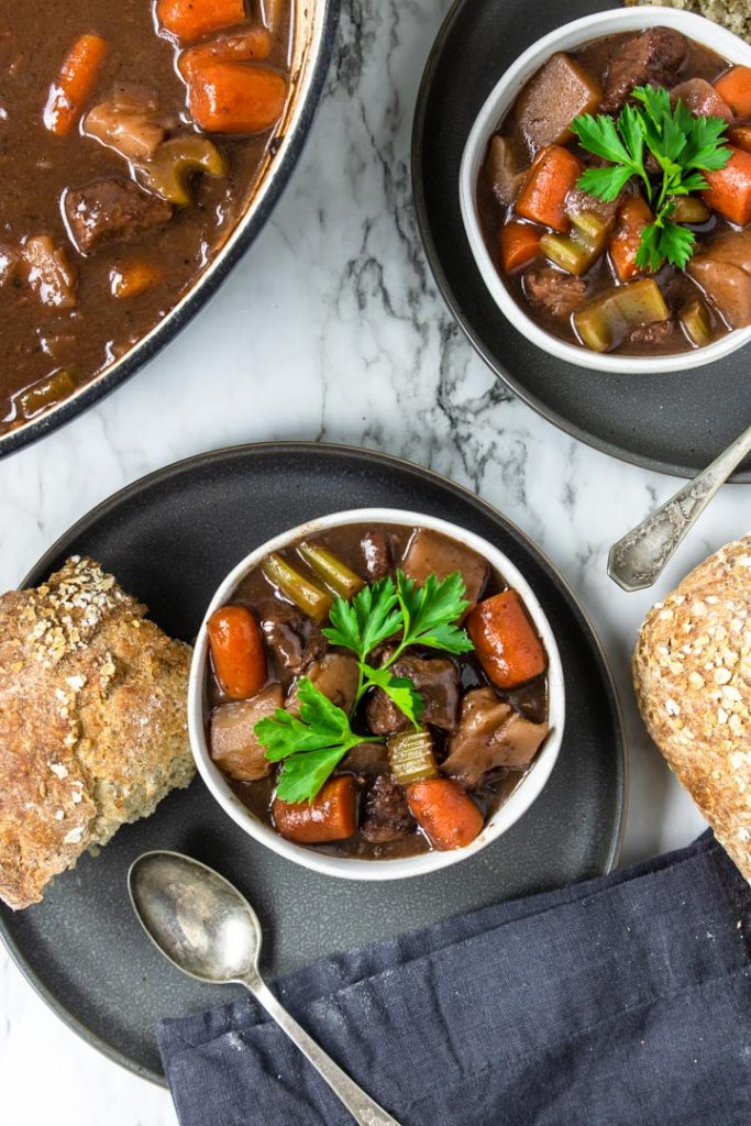 two bowls of beef stew with red wine served with crusty bread