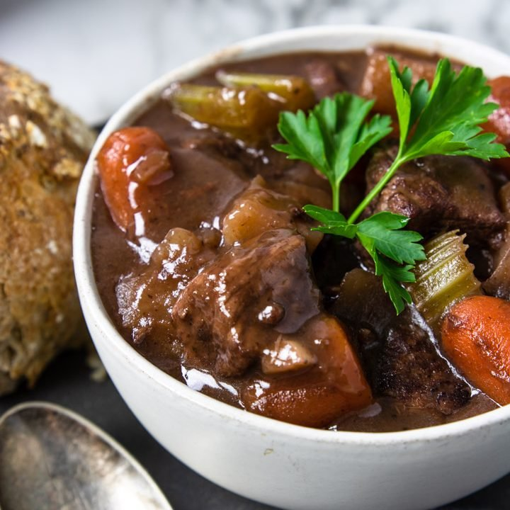 beef stew with red wine in a white bowl garnished with parsley