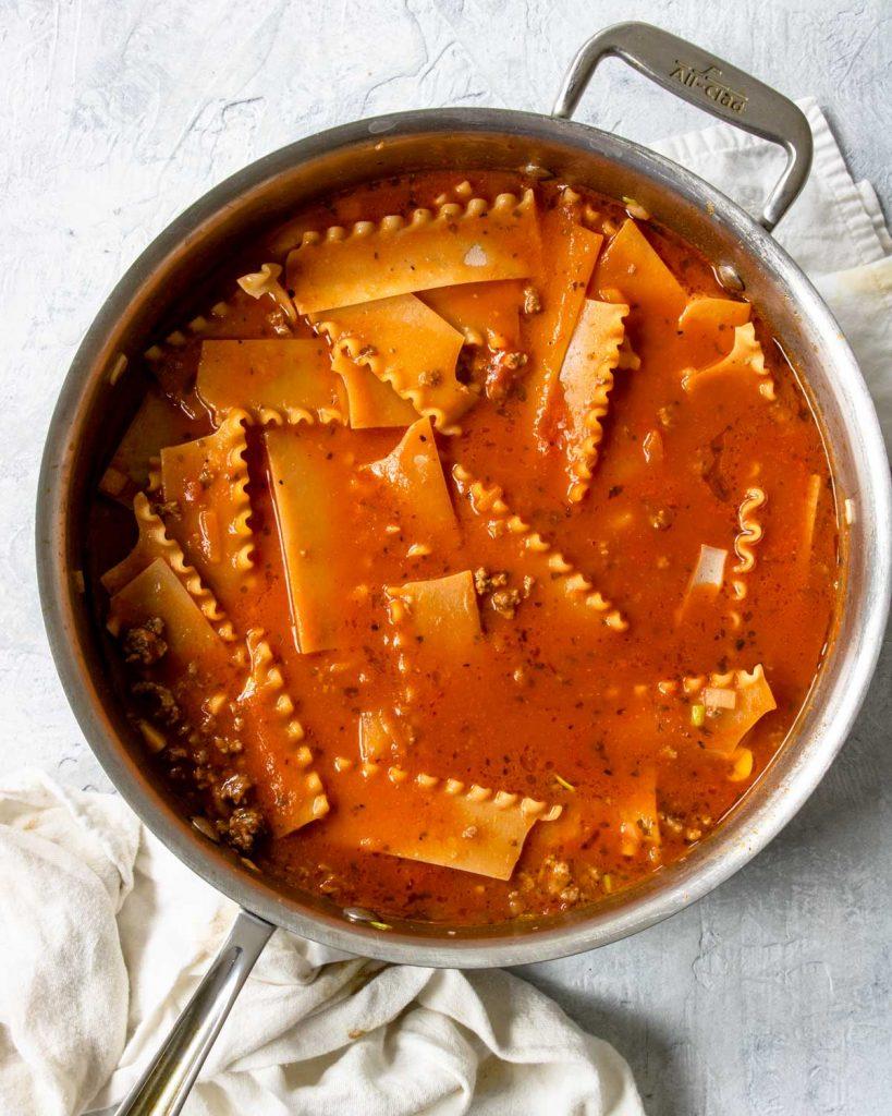 lasagna noodles nestled in sauce in a skillet