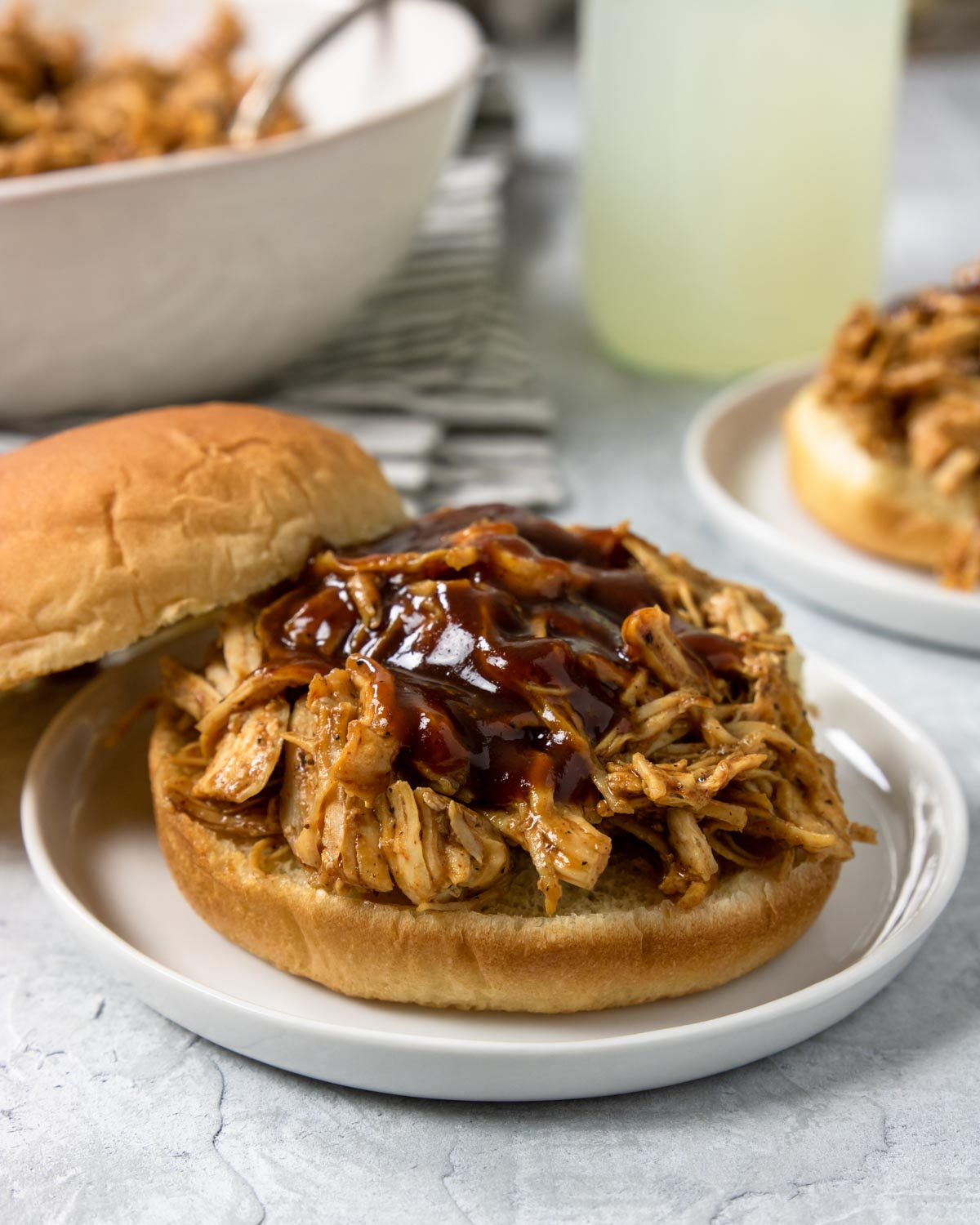 Instant Pot BBQ Chicken Sandwich on a white plate with lemonade in the background