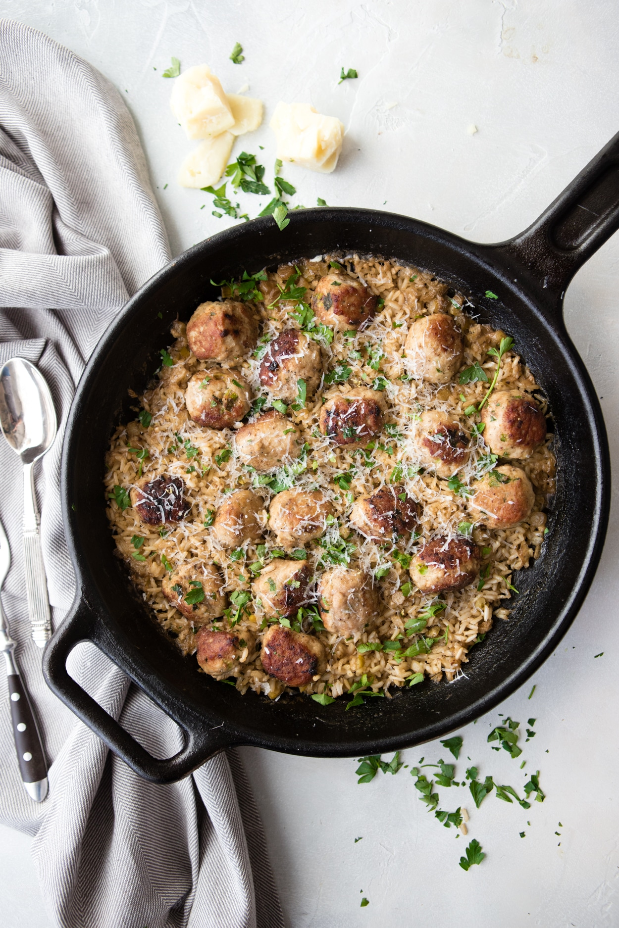 cast iron skillet with rice and meatballs