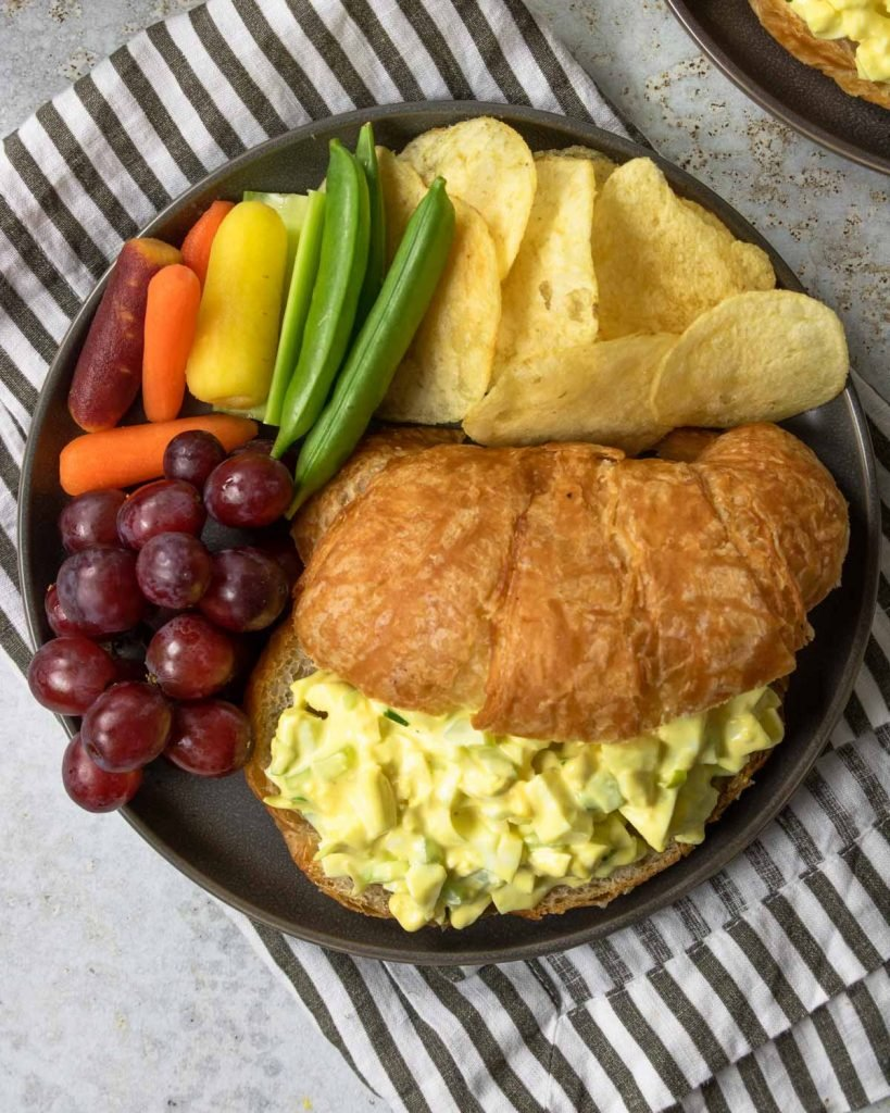 egg salad sandwich on a croissant with chips and veggies to the side