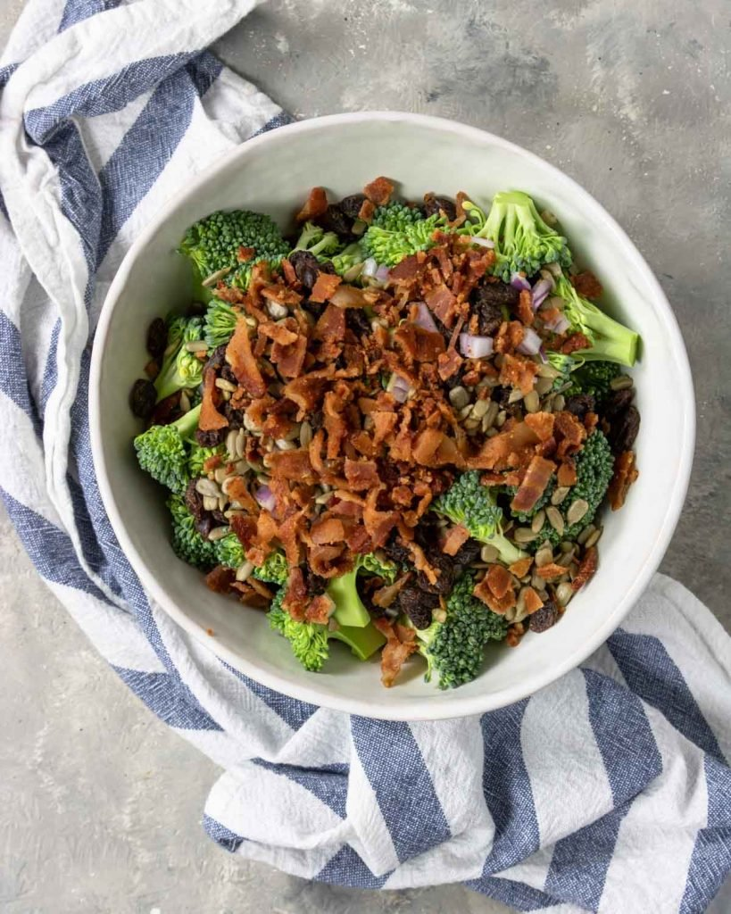 broccoli, onions, sunflower seeds and raisins in a bowl topped with bacon
