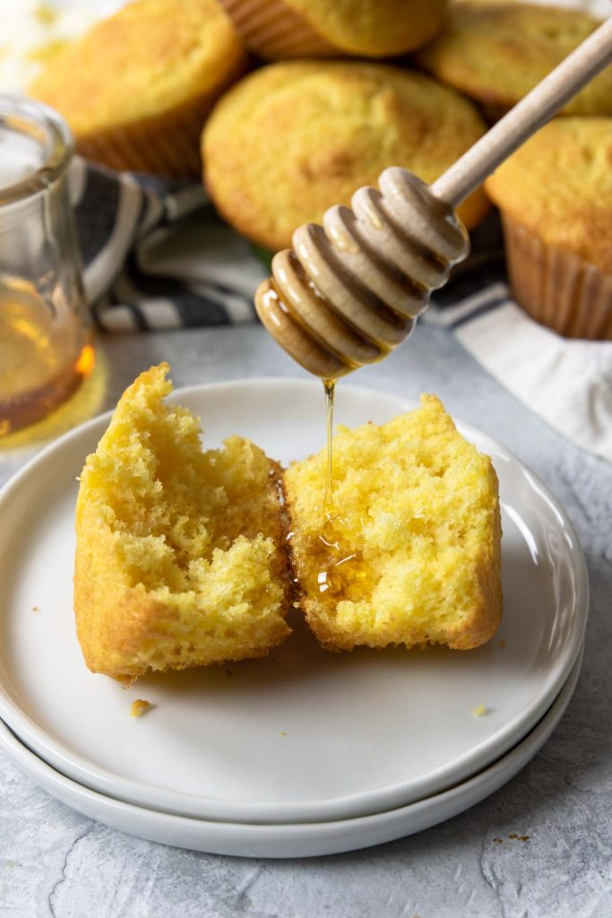 honey being drizzled on a corn muffin