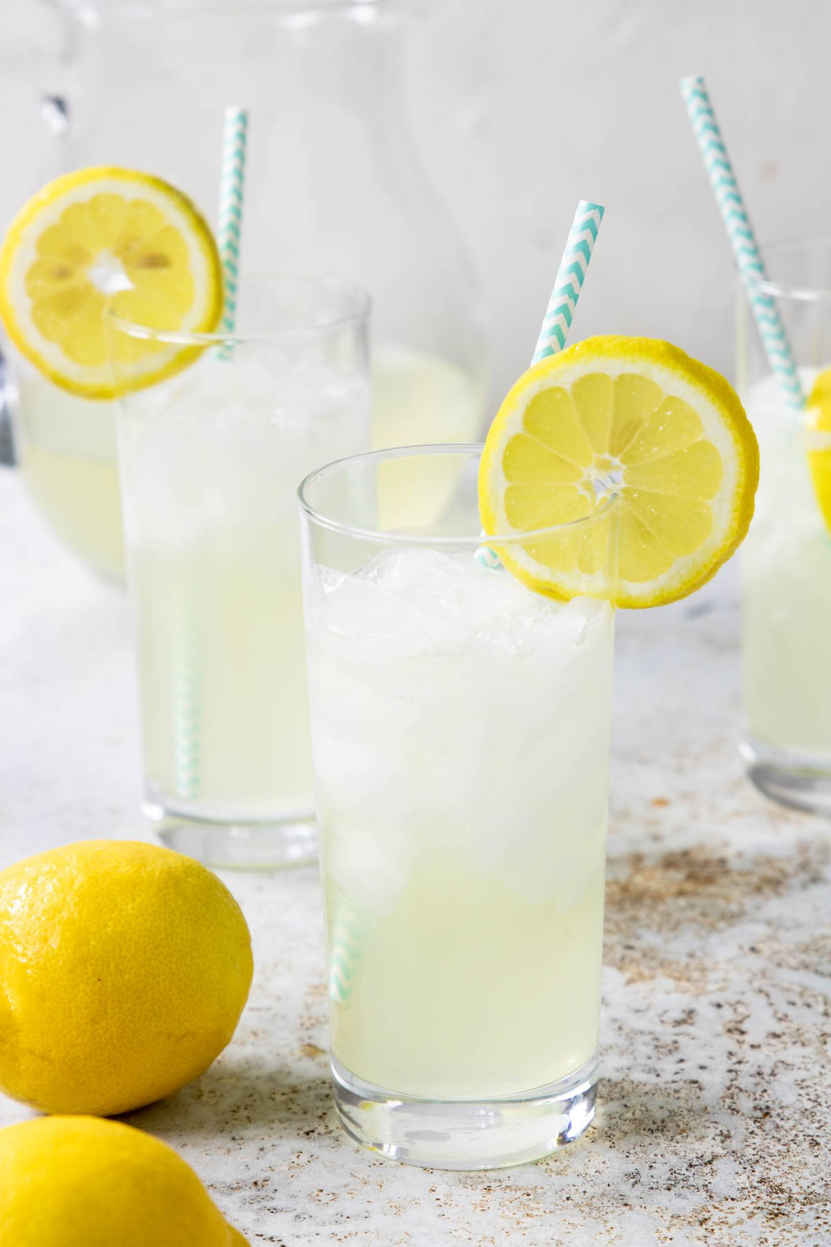 fresh squeezed lemonade in a glass with a lemon wheel and a blue paper straw