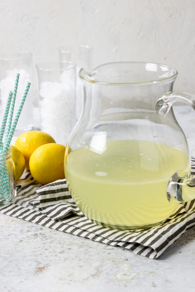 homemade lemonade in a glass pitcher with lemons to the side