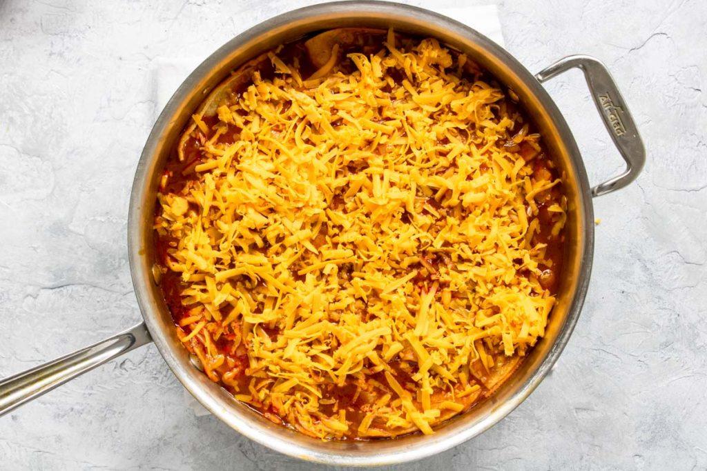 shredded cheese sprinkled on an enchilada skillet