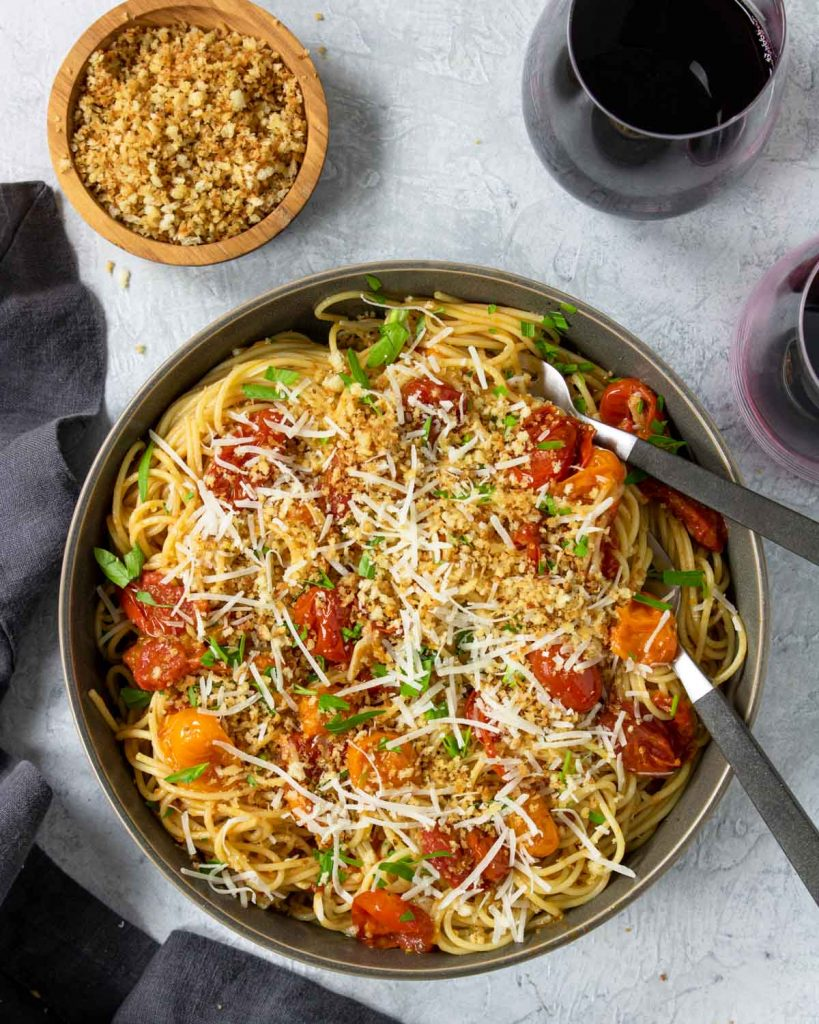 Pan Roasted Tomato Pasta in a bowl topped with bread crumbs and parmesan cheese