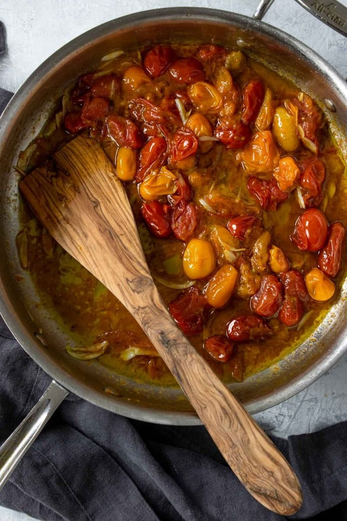 Cherry tomatoes that have been roasted in a skillet, with a wooden spoon in the pan