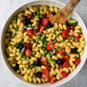 pasta salad with lots of veggies that has been all stirred together in a white bowl