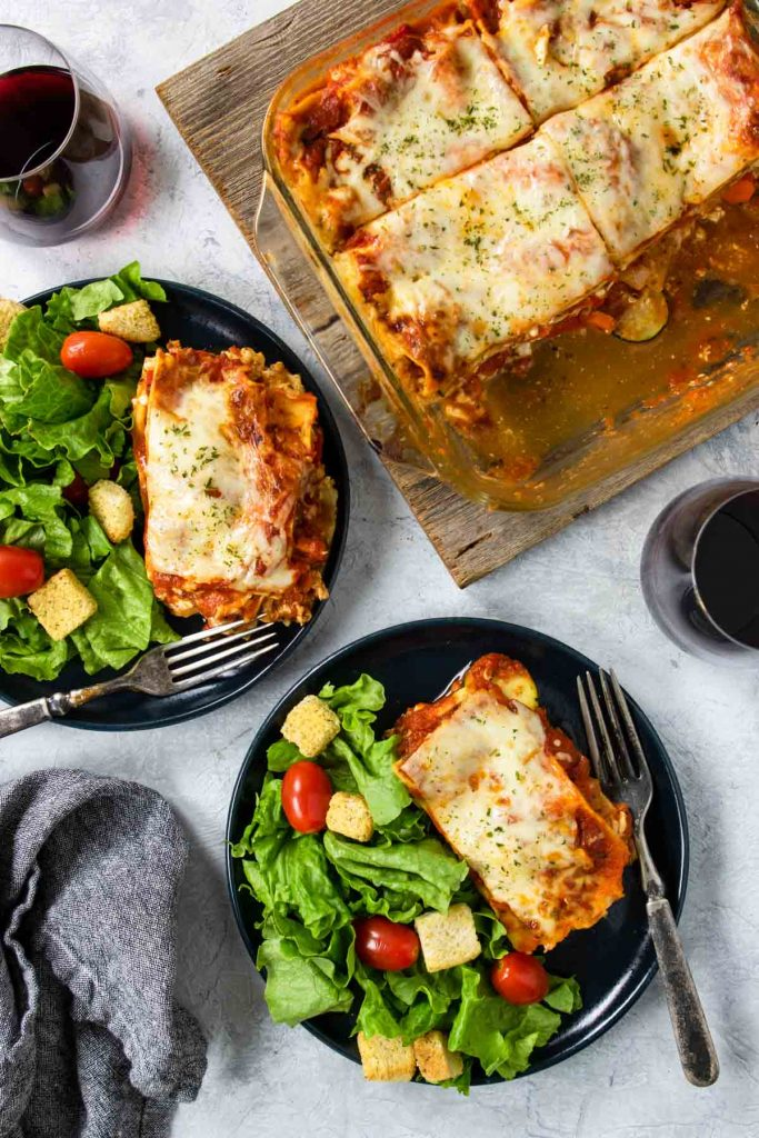 two blue plates with a slice of veggie lasagna and salad, and a glass baking dish of lasagna