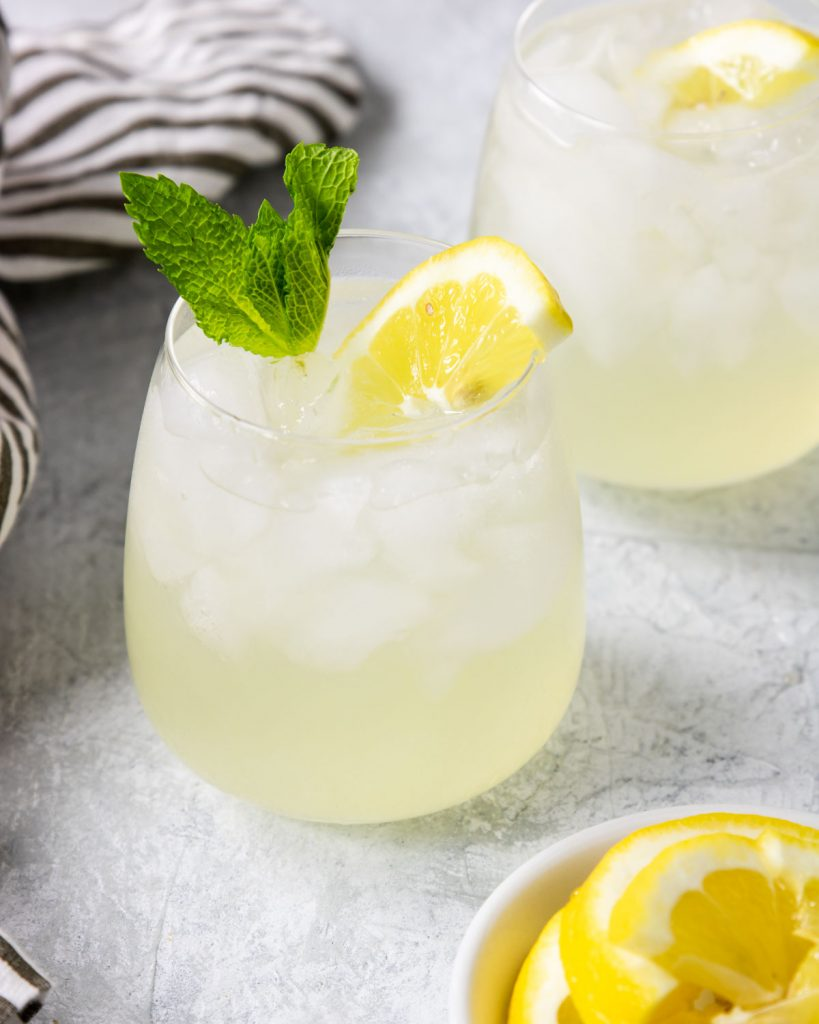 vodka with fresh lemonade in a small glass with a mint sprig and fresh lemon