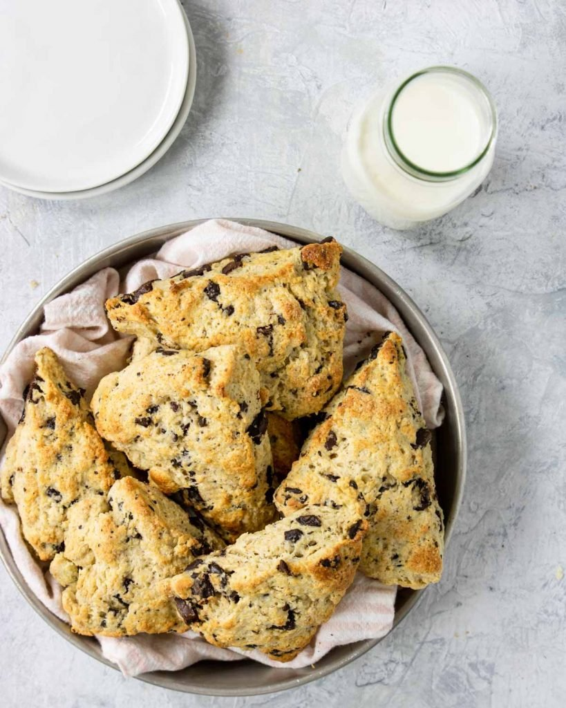 a jug of milk and a basket of chocolate chip scones