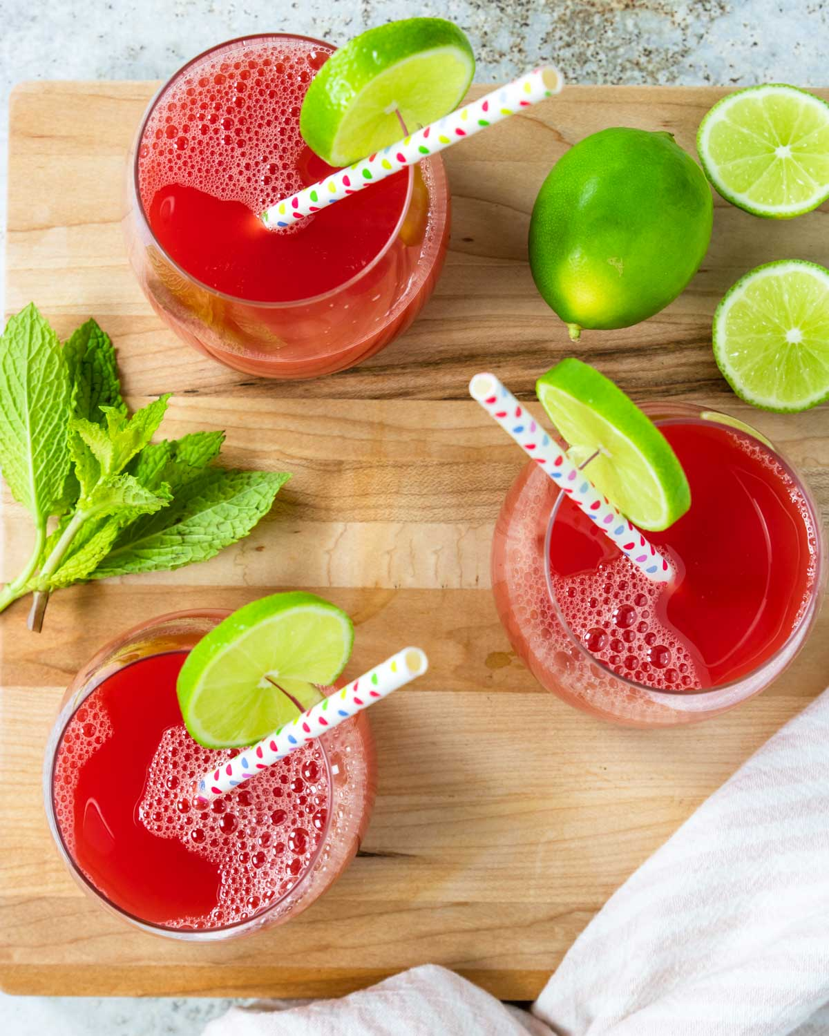 three glasses of watermelon juice from above garnished with limes
