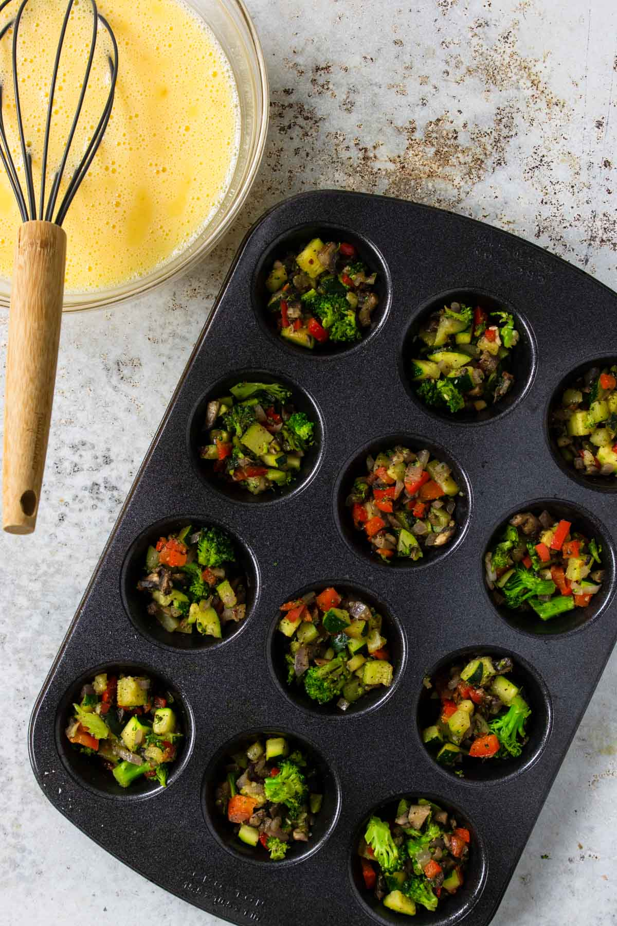 muffin tin full of veggies and an egg mixture to the side