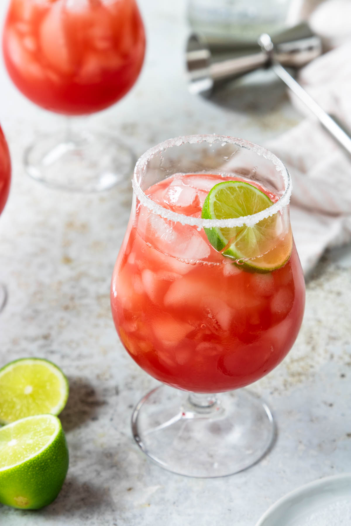 a glass of fresh watermelon margarita rimmed with sugar and salt and garnished with a lime