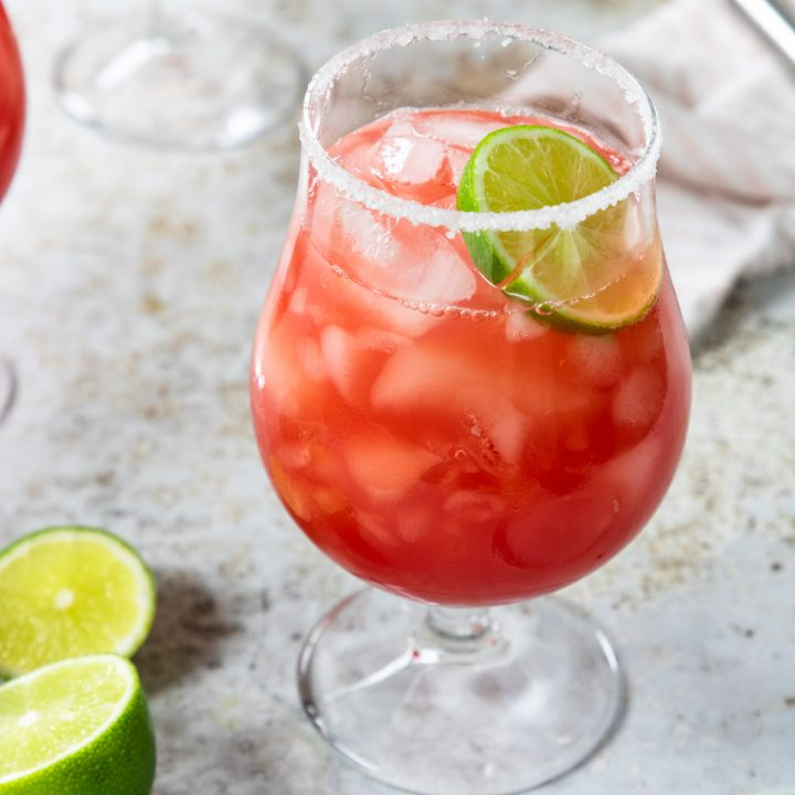 a watermelon margarita in a stemmed glass with a sugar-salt rim and a lime garnish