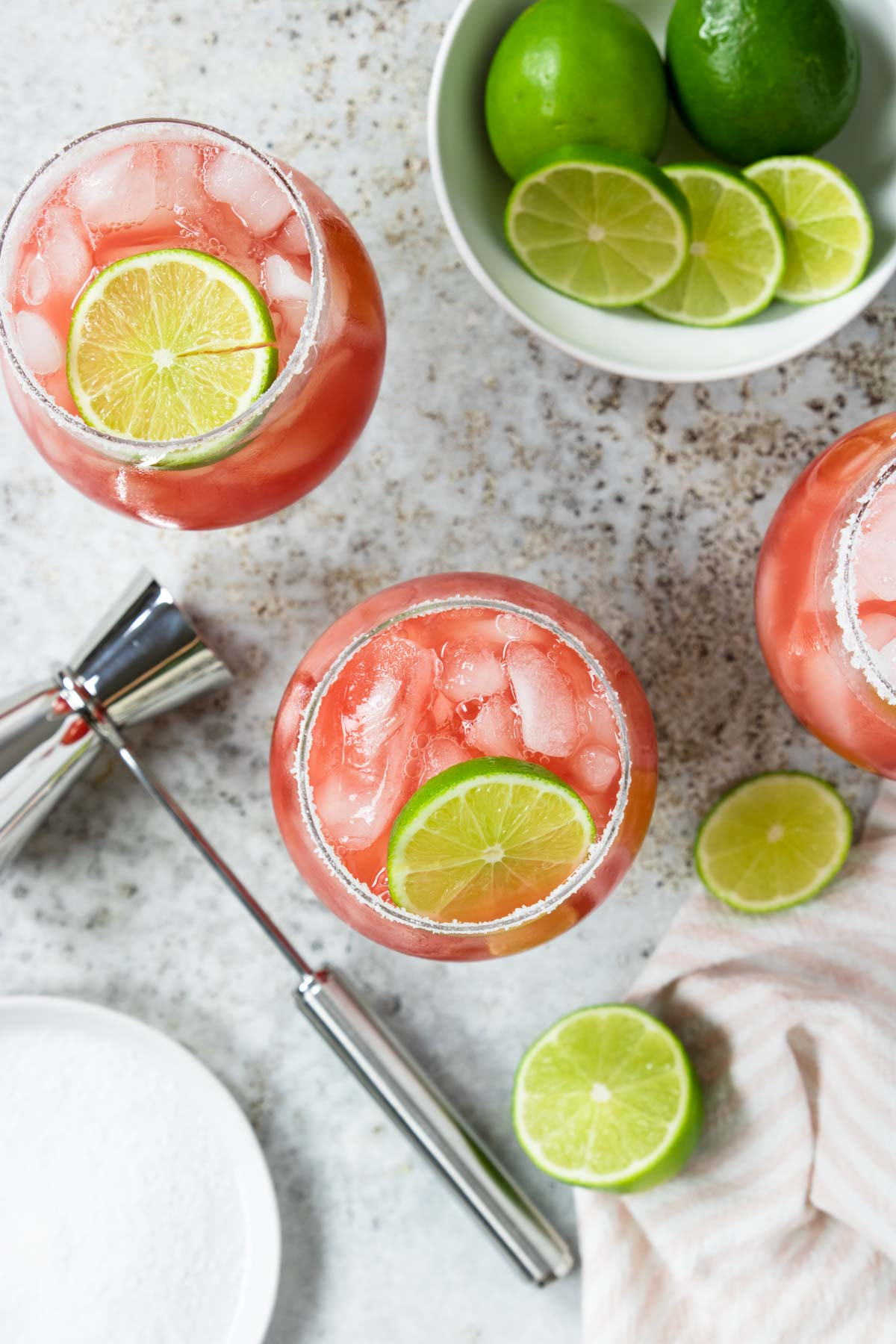 watermelon margaritas photographed from above showing the drink in the glass and a bowl of limes