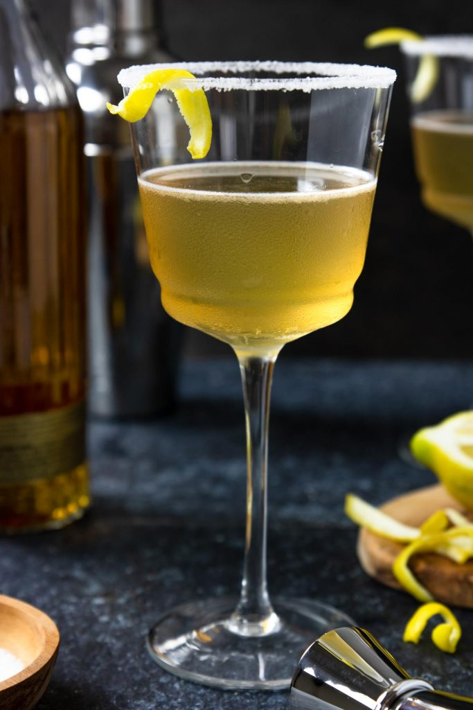 Anejo Sidecar in a stemmed glass with a sugar rim and lemon peel. Anejo tequila bottle to the side