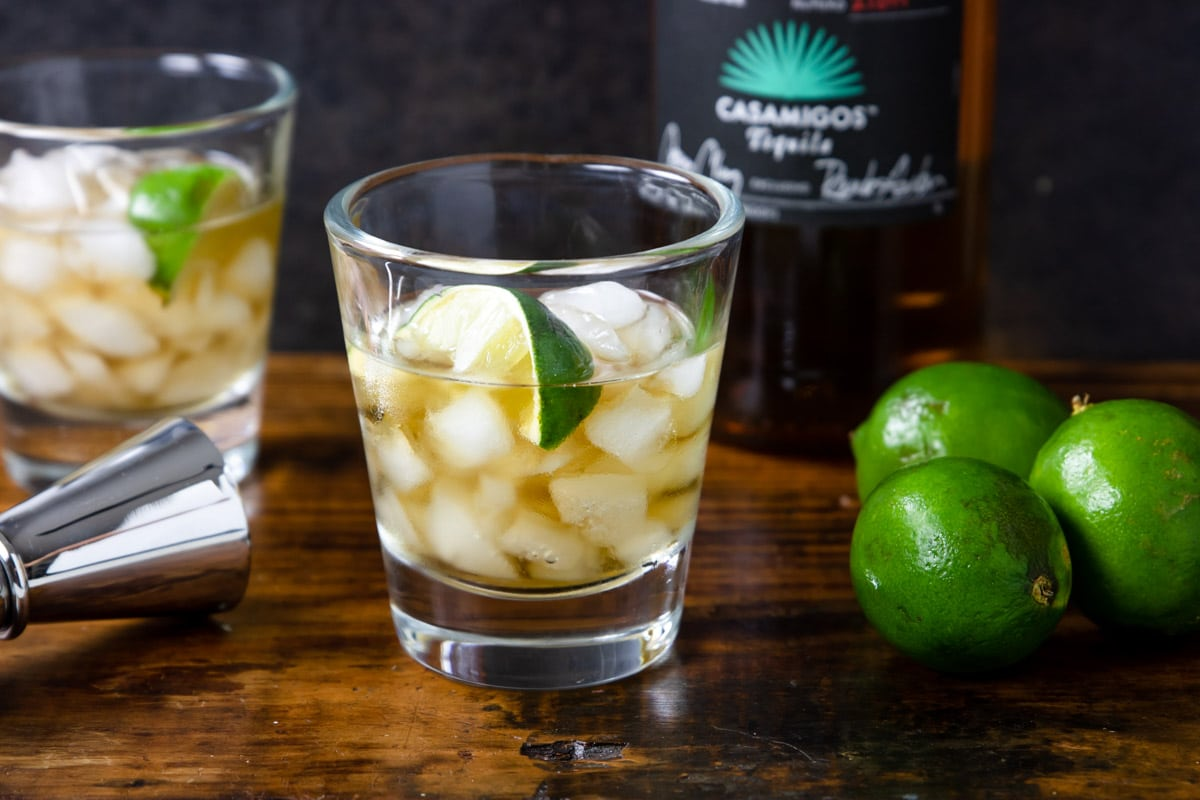 two glasses of tequila on the rocks on a wooden surface with a bottle of tequila and three limes to the side