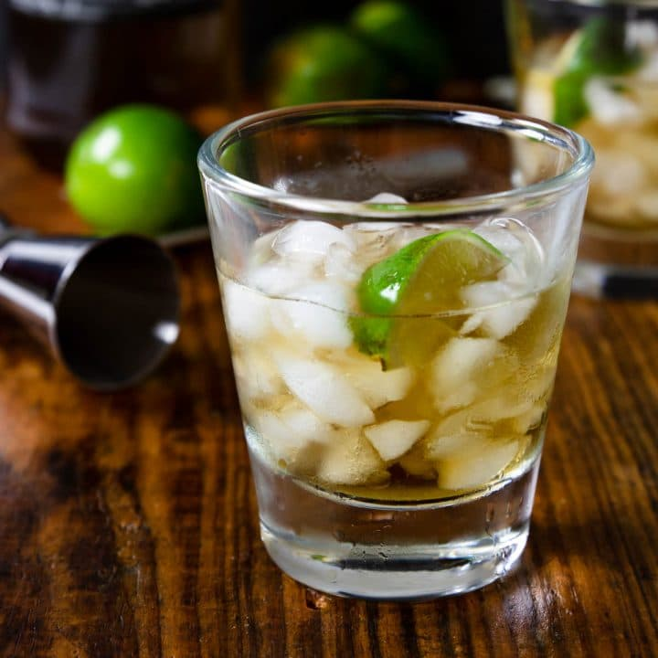 a glass with anejo tequila on the rocks with a lime