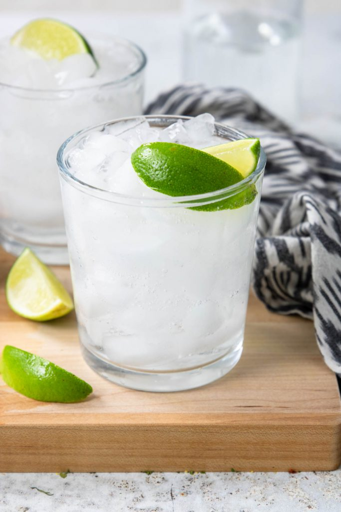 A glass filled with ice, tequila and soda and topped off with two limes