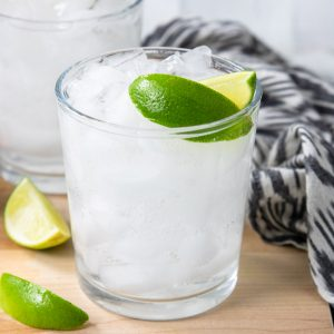 a cocktail glass filled with ice, tequila, and soda water, topped off with two lime wedges