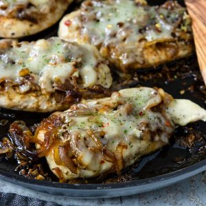chicken breasts topped with an onion jam and melted cheese, in a skillet